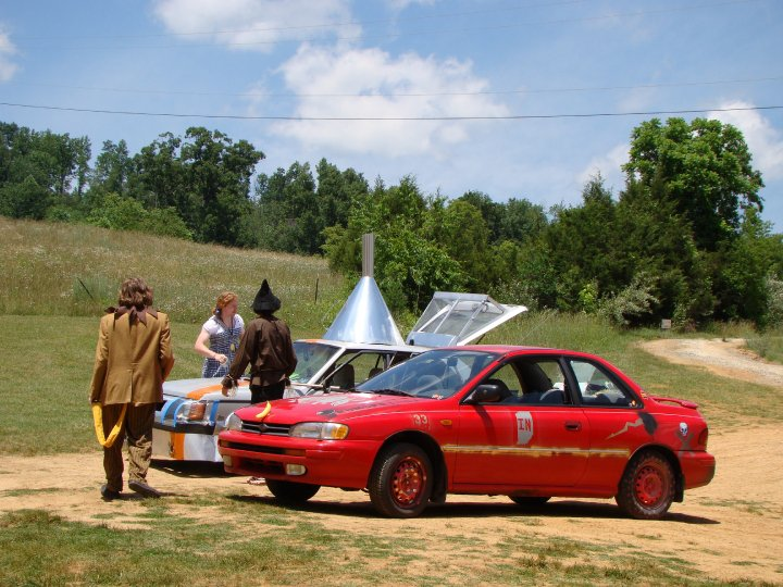 scavengers hunters dressed as characters from the Wizard of Oz, gather around their customised car which looks like the Tin Man