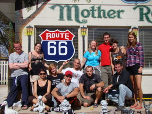 Western USA: group stood in fron ot Route 66 sign in Seligman